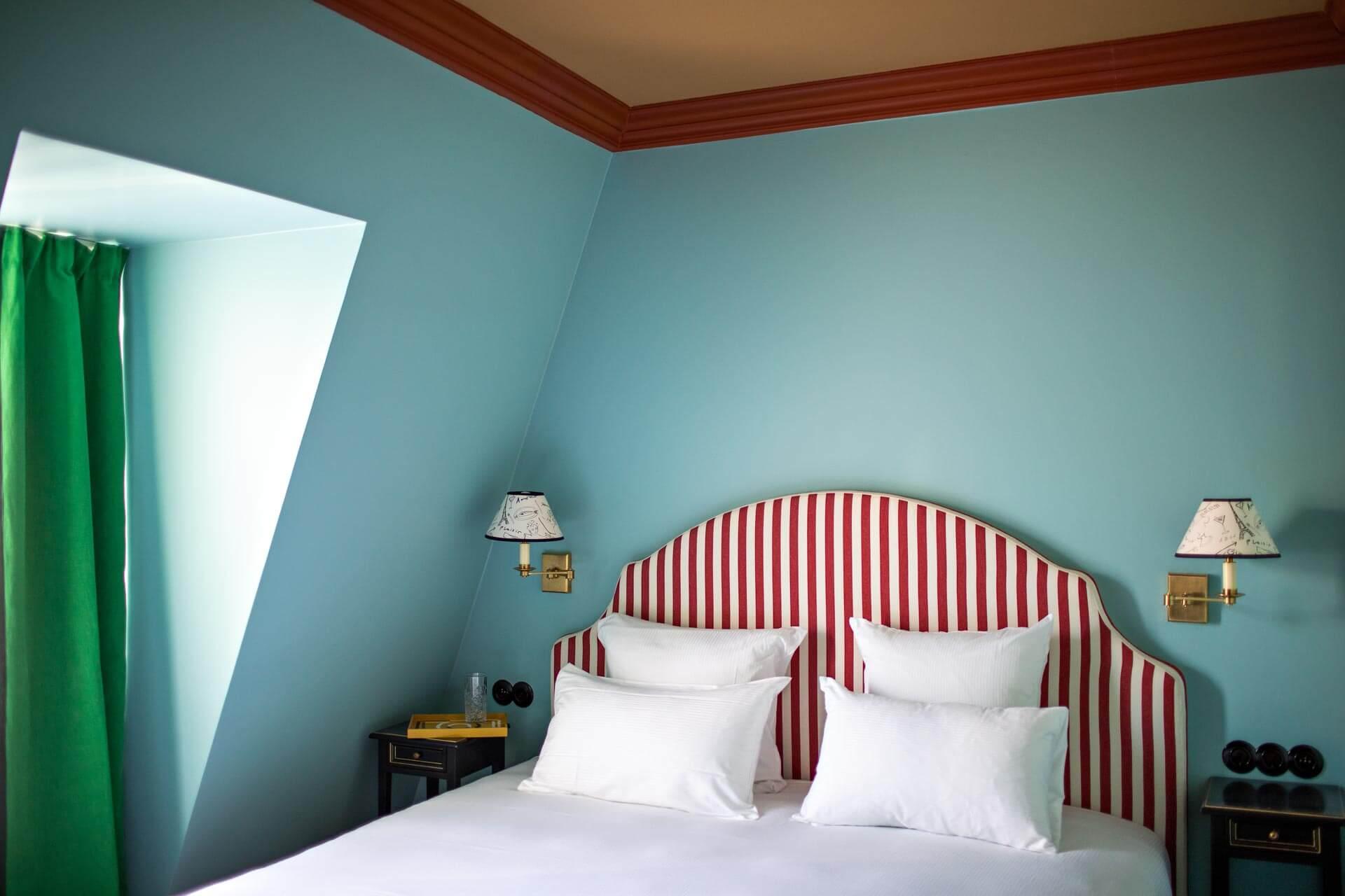Une des chambres bleues avec sa tête de lit rayée et se lampes 70's © DR