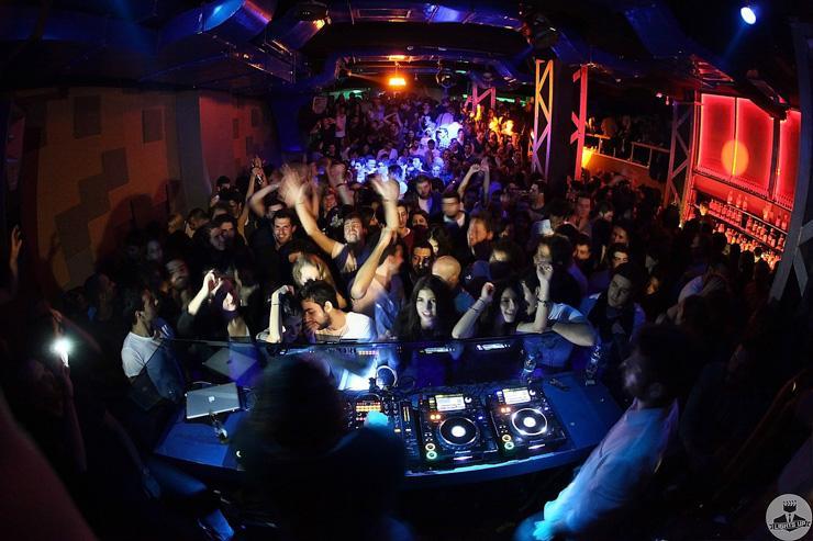 Indigo Club - Foule de clubbers derrière le DJ booth