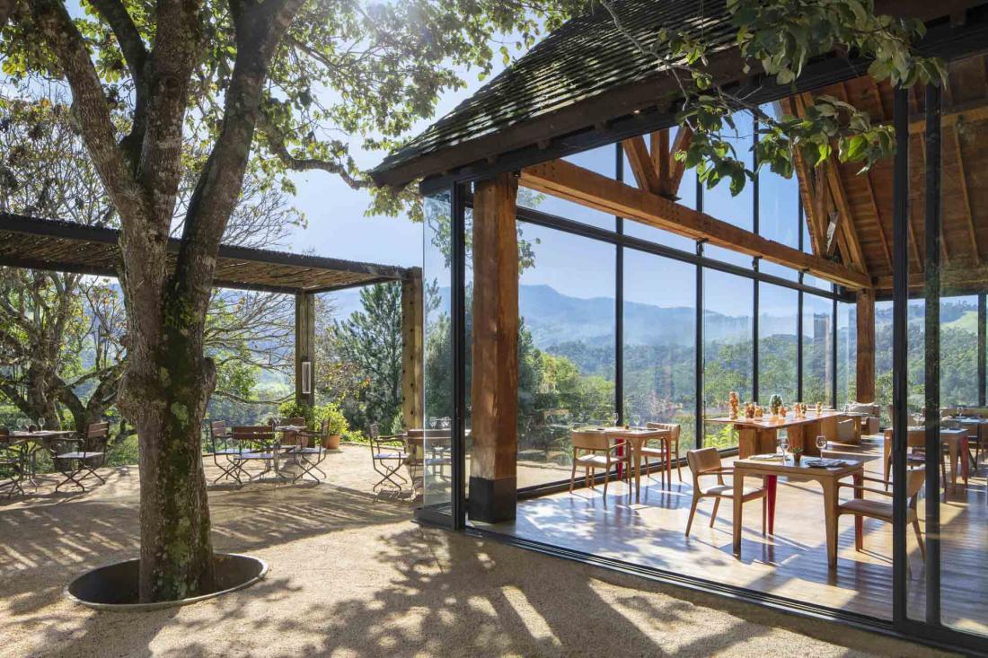 La spacieuse terrasse du restaurant à flanc de colline est ombragée par des auvents naturels