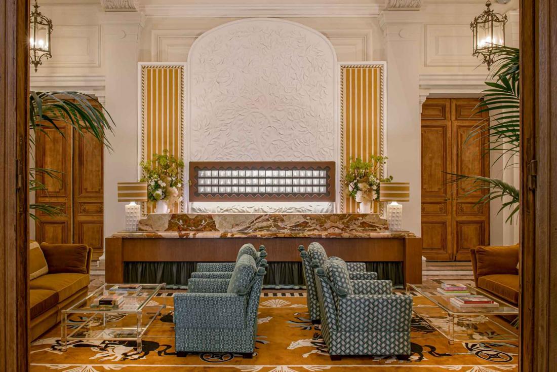 Un lobby de grand hôtel où rien ne manque : panneau à clé, desk en marbre et fauteuils confortables
