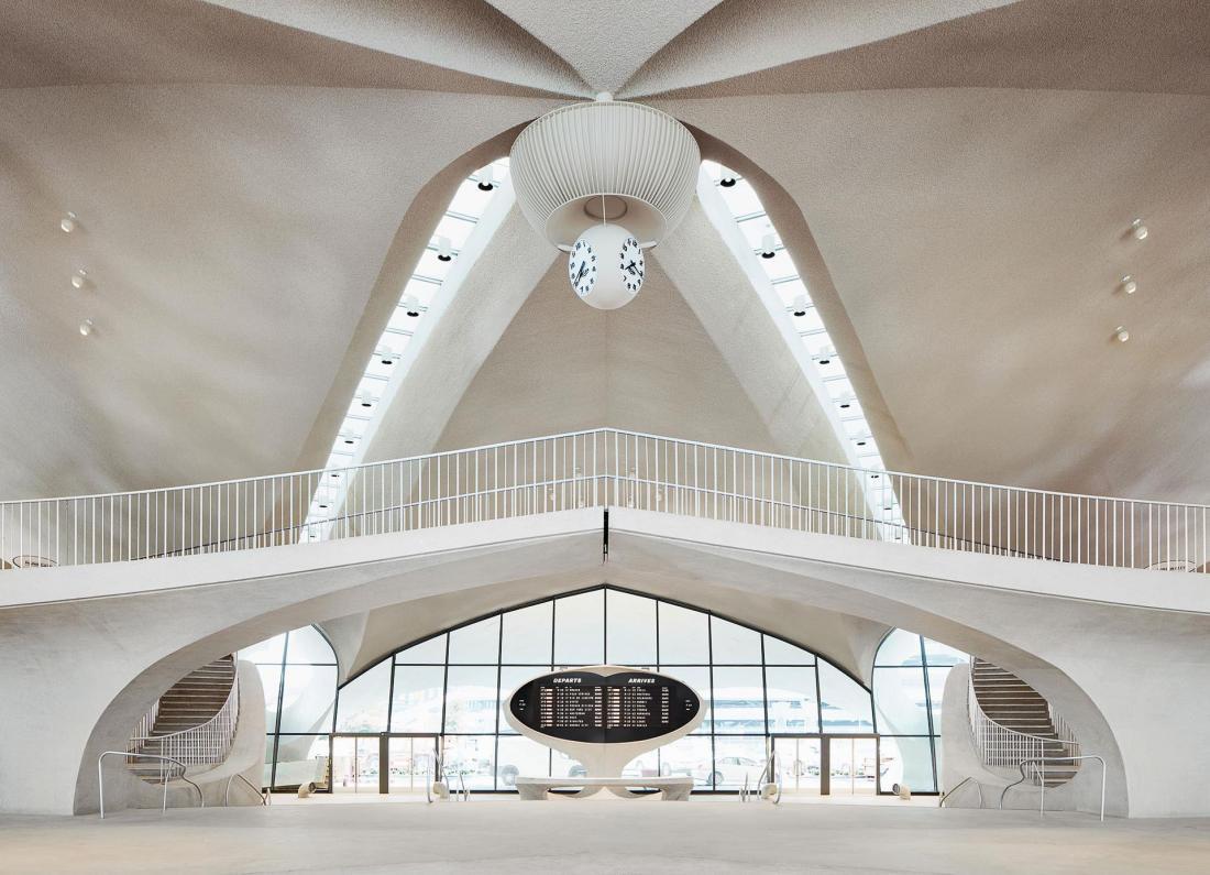 L'immense lobby en béton brut habillé est habillé de la réédition d'un afficheur à palette.