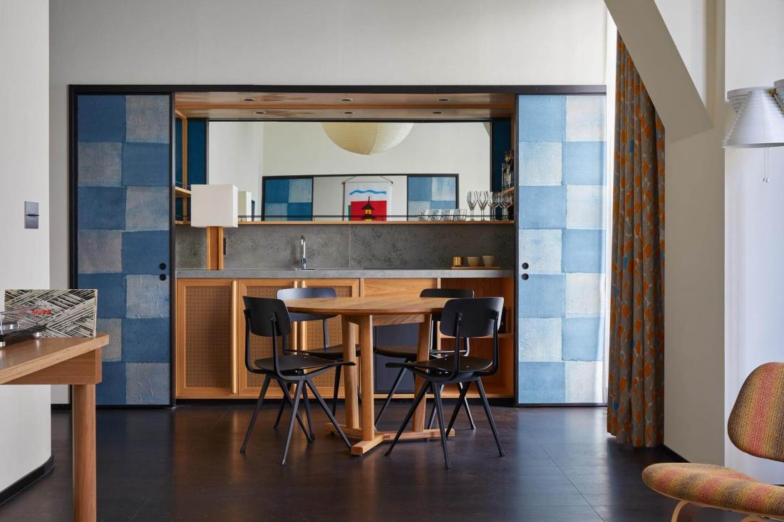 Des panneaux colorés coulissants dévoilent un espace bar dans la Ace Suite