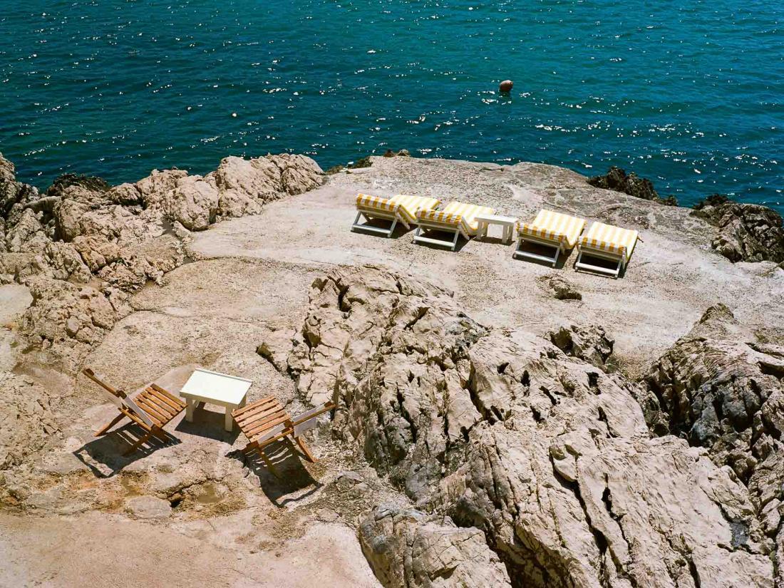 A l'extérieur, matelas aux rayures et tables en bois sur un plage rocheuse