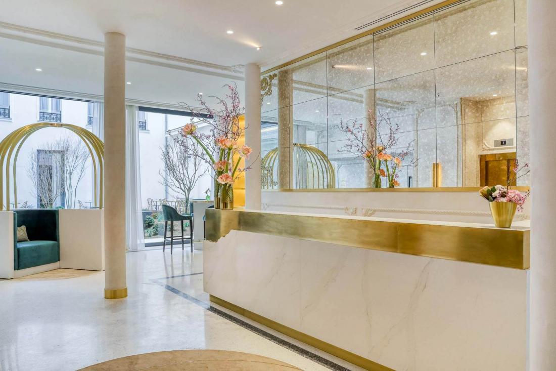 Le lobby lumineux en marbre s'ouvre sur le restaurant et le jardin
