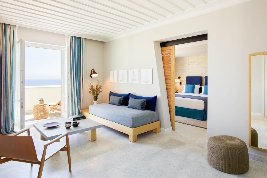 Une suite familiale pour 4 avec un grand espace séjour équipé de deux canapés-lits, une chambre queen-size privée et un balcon relaxant