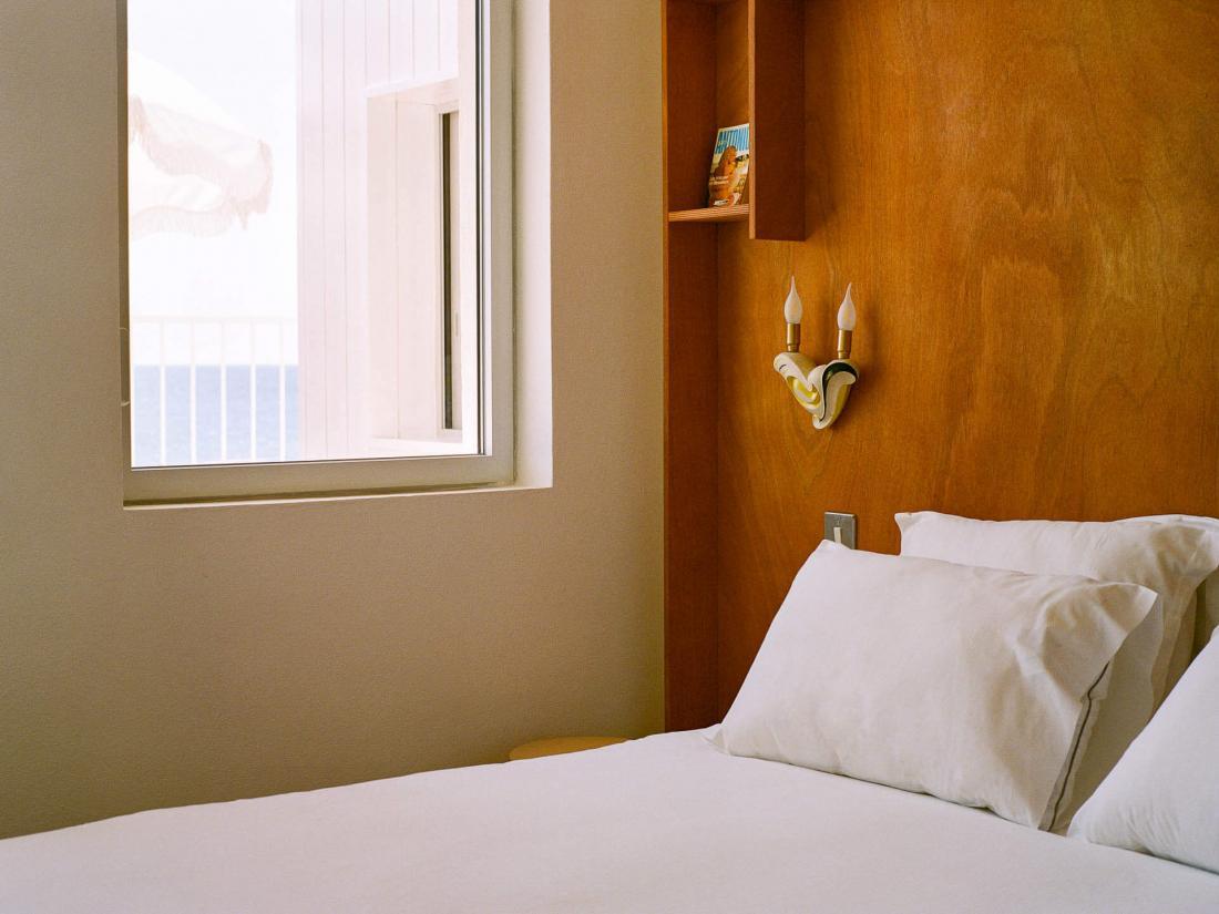 Les chambres minimaliste avec jonc de mer au sol, draps blancs, lampes en cordages, têtes de lit en contreplaqué