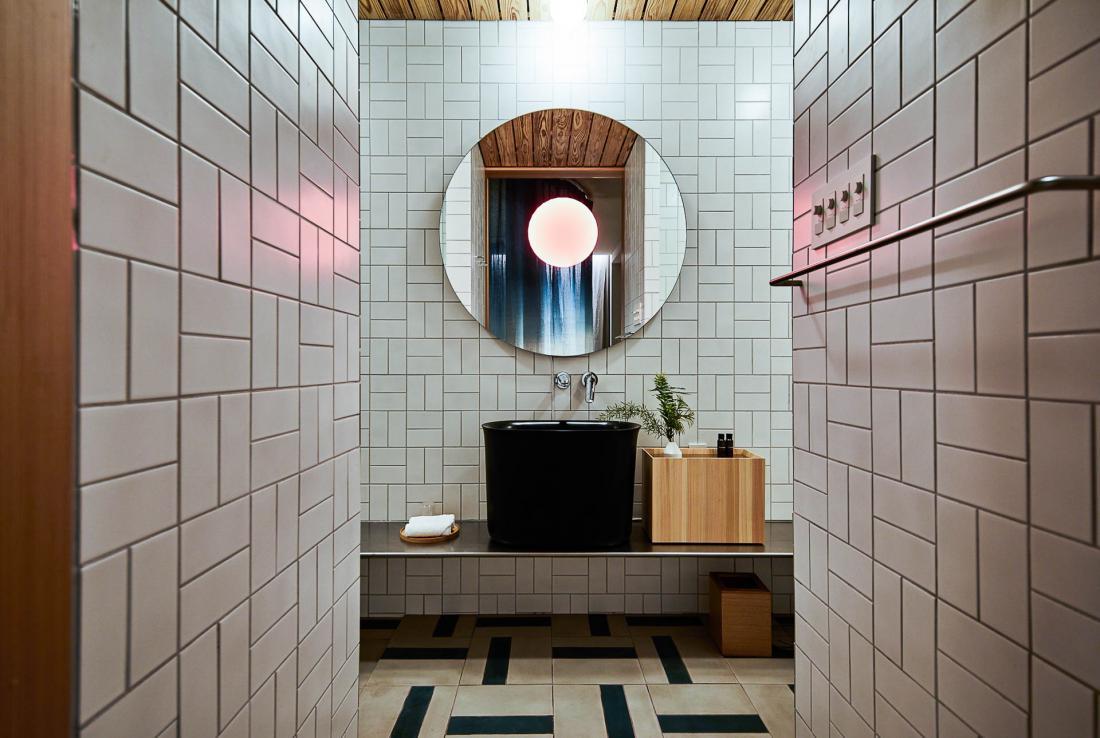 Jusque dans la salle d'eau, l'hôtel puise ses inspirations des traditions, ici les baquets en bois de cèdres des onsen