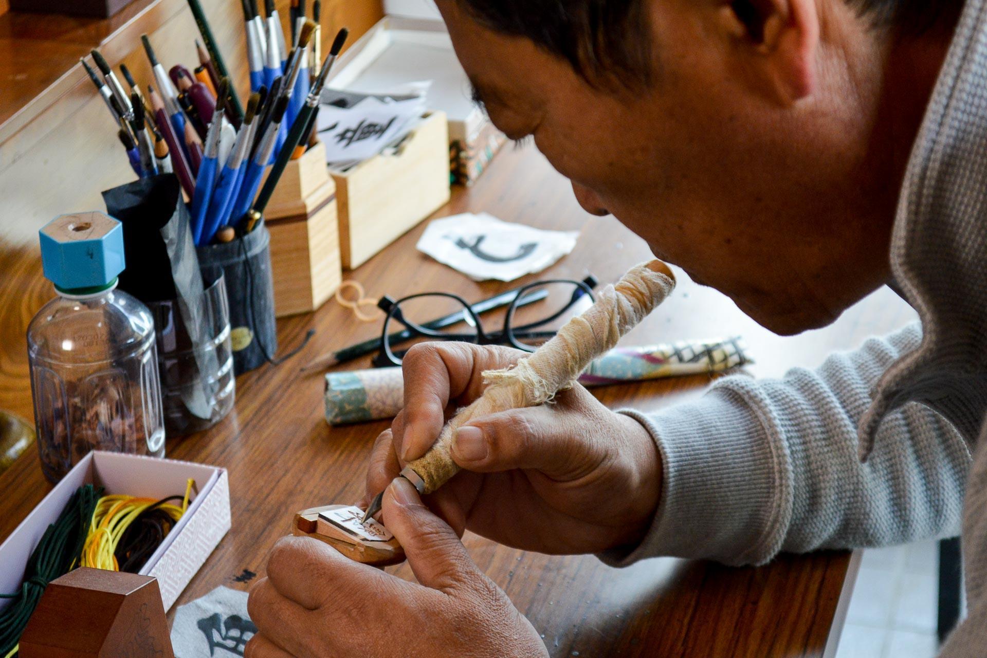 Monsieur Nakajima sculpte la pièce de shogi appelée général d'argent.