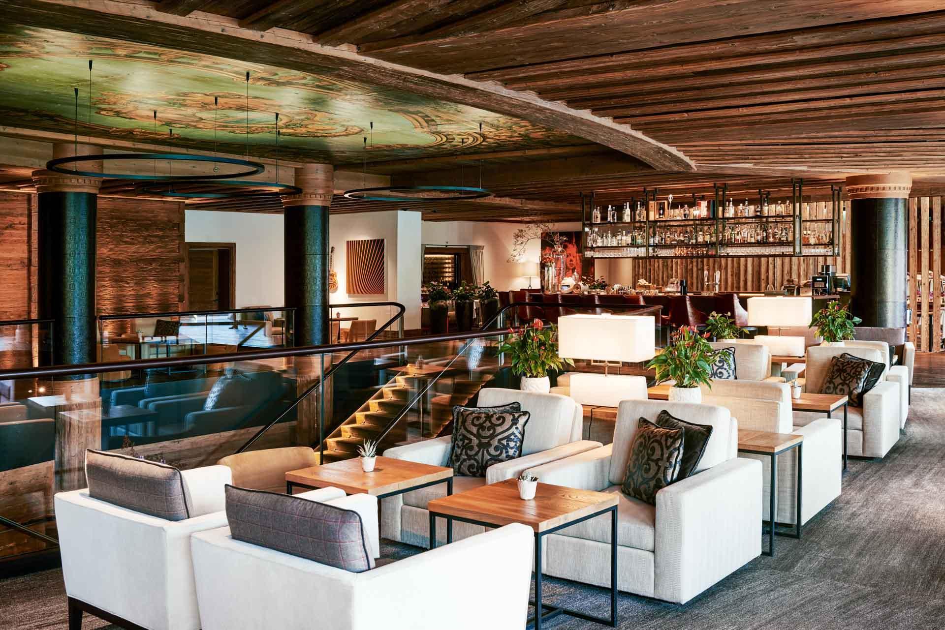 Boire un verre avant le dîner à l'Alpina Lounge & Bar, ouvert sur le jardin par de grandes ouvertures © The Alpina Gstaad