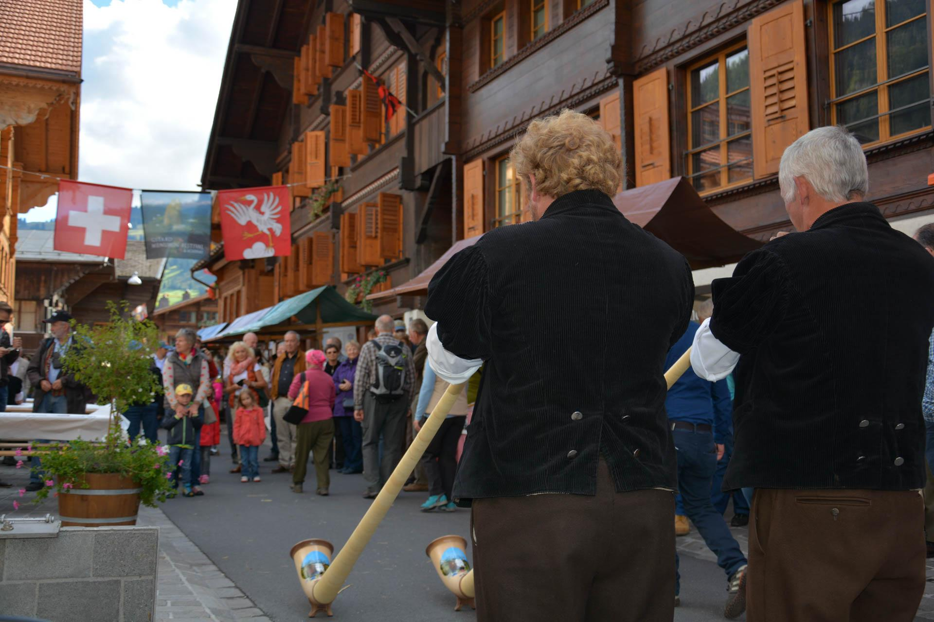 Des habitants jouent du Cor des Alpes lors du marché aux fromages à Saanen © Destination Gstaad