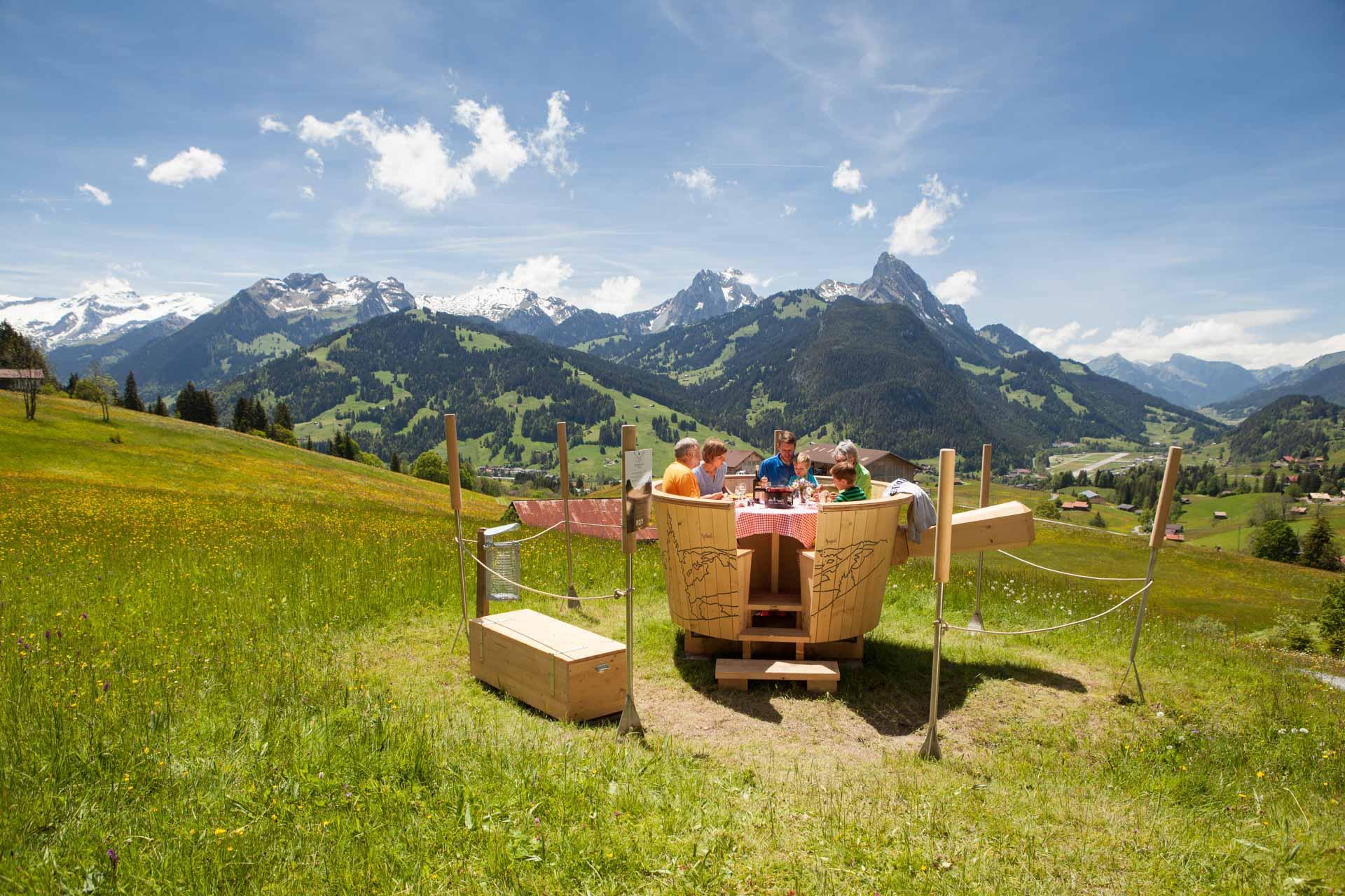S'installer à une table face aux montagnes pour une fondue en plein air © Destination Gstaad.
