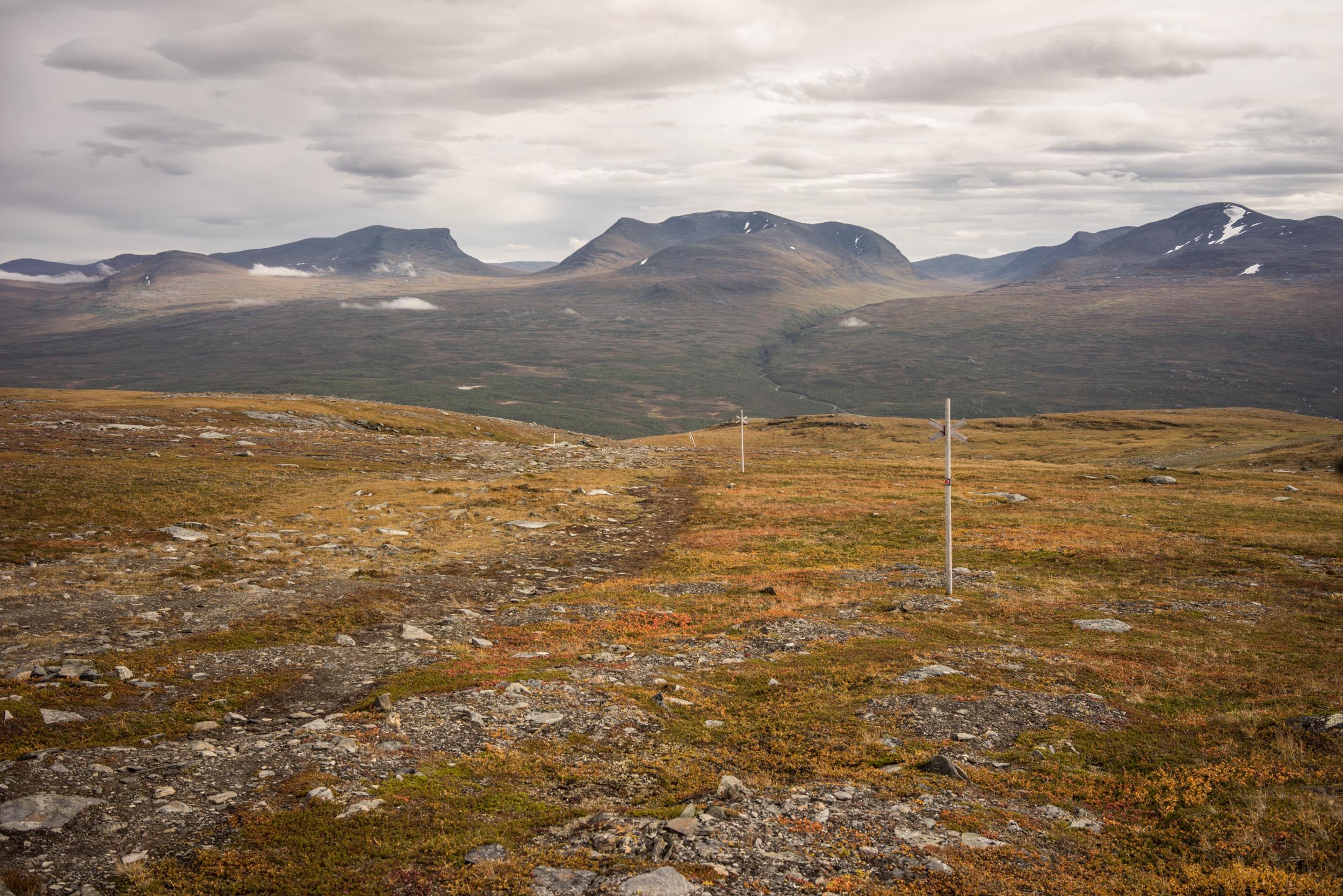 """Depuis la station supérieure, la randonnée vers le sommet est courte et facile. Le paysage verdoyant a cédé la place à la  toundra. Au fond à gauche on distingue la vallée """"iconique"""" de Lapporten, archétype d'une vallée en U creusée par les glaciers."""