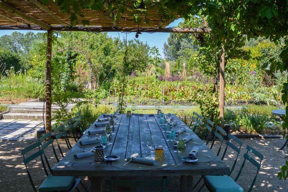 Les grandes tablées en bois face au jardin accueillent les convives en été © Pierre Gunther