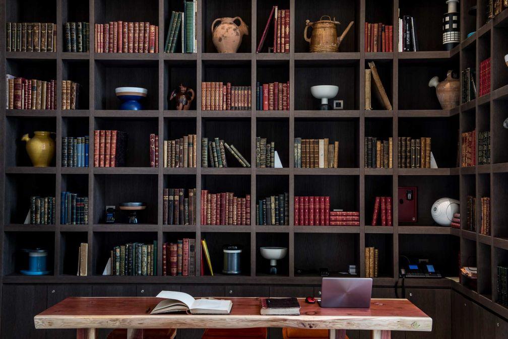 Derrière le bureau de la réception, une immense bibliothèque © Anne-Emmanuelle THION