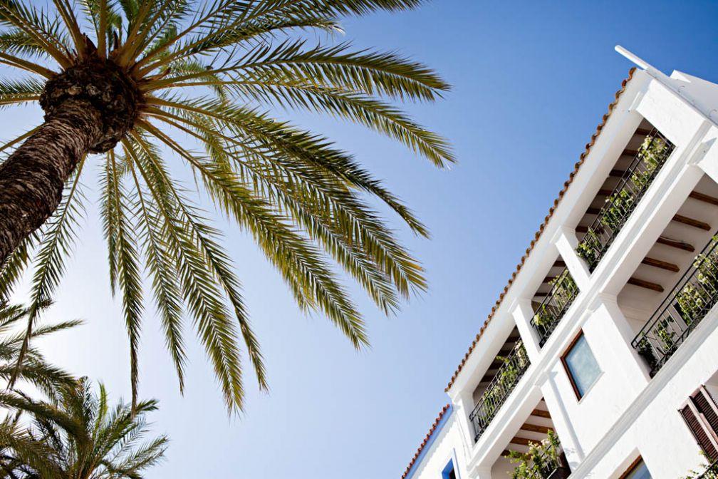 Façade blanche et palmiers, bienvenue aux 105 Suites © Yann Deret