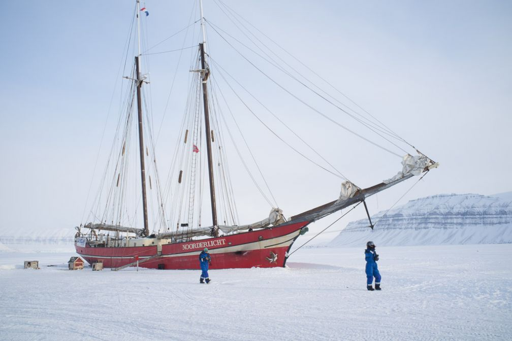 Le <i> Noorderlicht </i> hiverne sur le fjord gelé de Tempelfjorden. Il est possible de déjeuner ou de passer la nuit à bord en réservant un tour avec Basecamp Spitsbergen.
