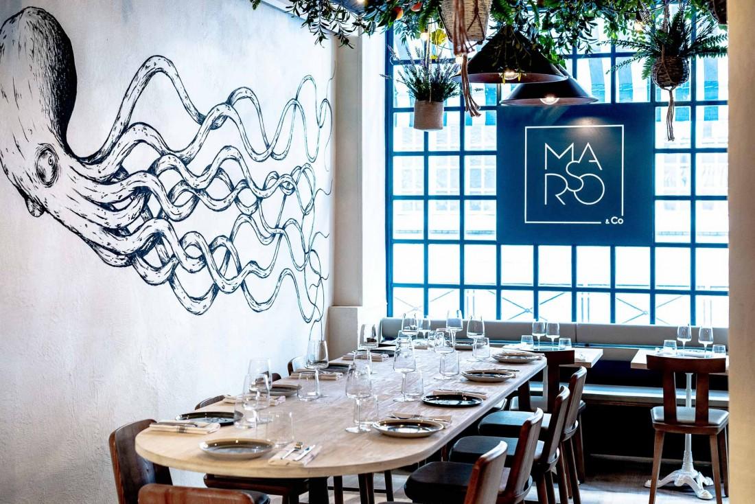 Intérieur du restaurant Marso&co avec sa grande table d'hôtes. Au mur, l'une des fresques de Kraken, street artist parisien renommé © Caspar Miskin