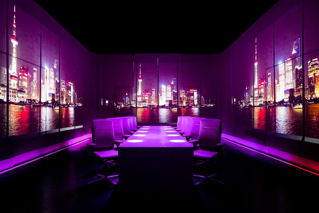 Au centre de la salle à manger d'Ultraviolet by Paul, une table pour dix convives. Sur les murs, une projection d'une vue de Shanghai © Scott Wright