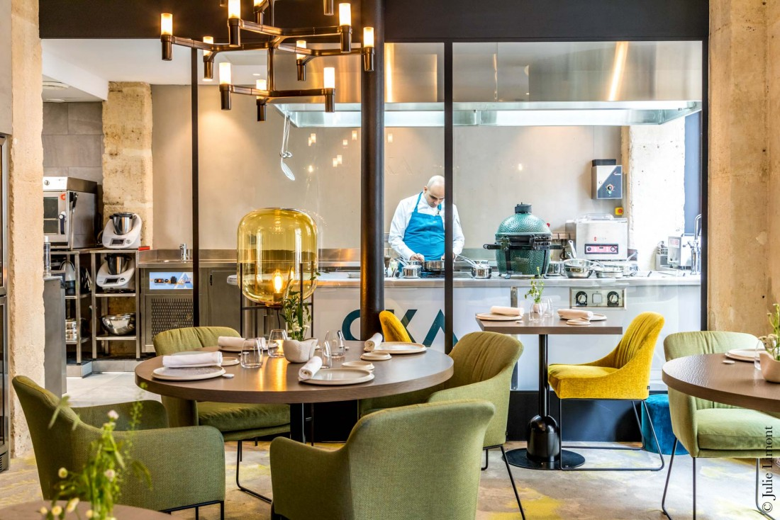 À l'intérieur du Restaurant OKA : salle à manger confortable, touches colorées et spectaculaire cuisine vitrée © Julie Limont