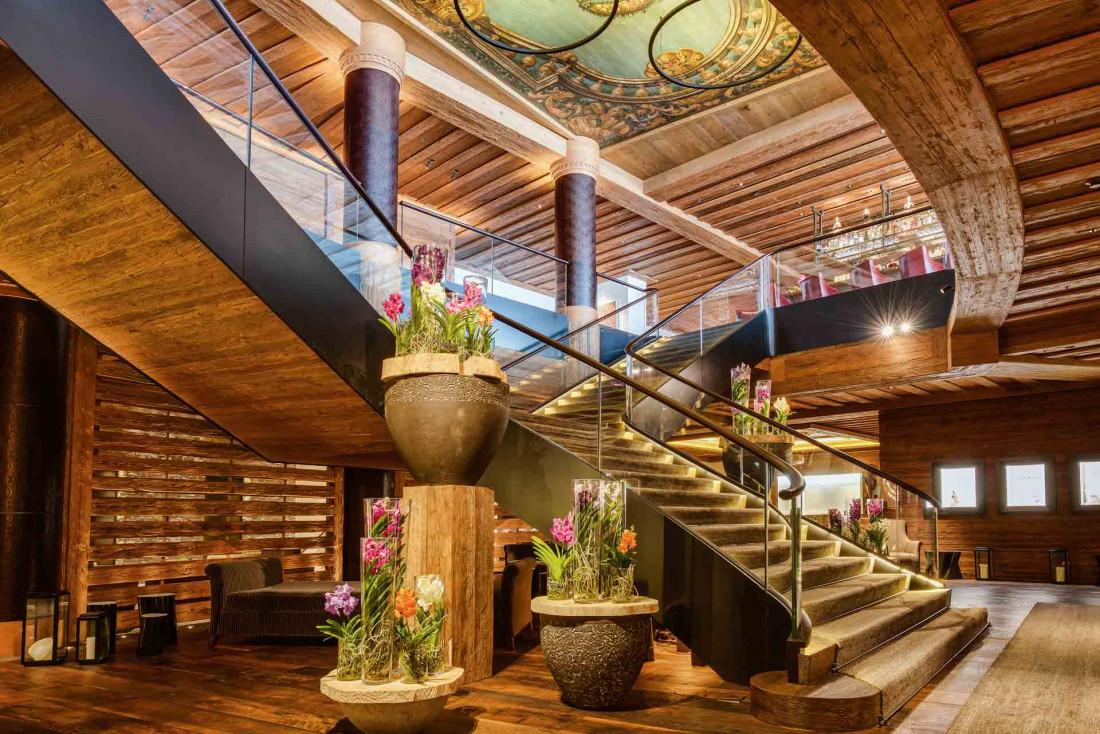 Arrivée dans le lobby face à son double escalier, sous un plafond peint baroque © The Alpina Gstaad