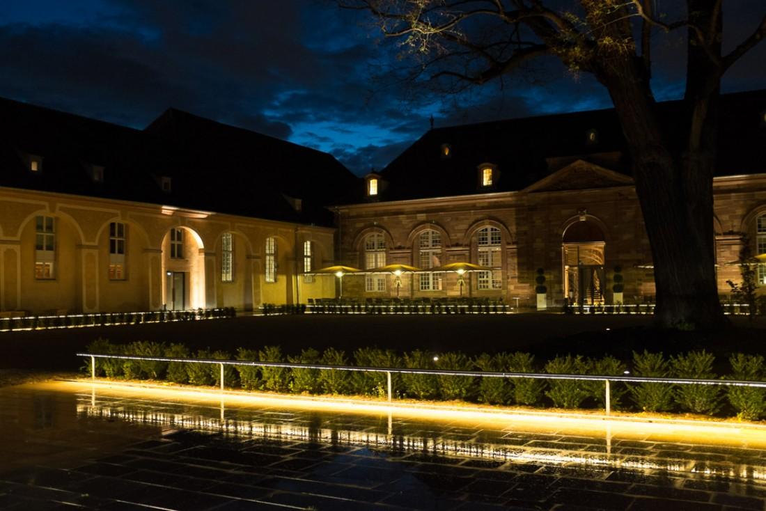 La grande cour vue de nuit, où s'exerçaient autrefois les chevaux des haras. La brasserie occupe le bâtiment de droite.