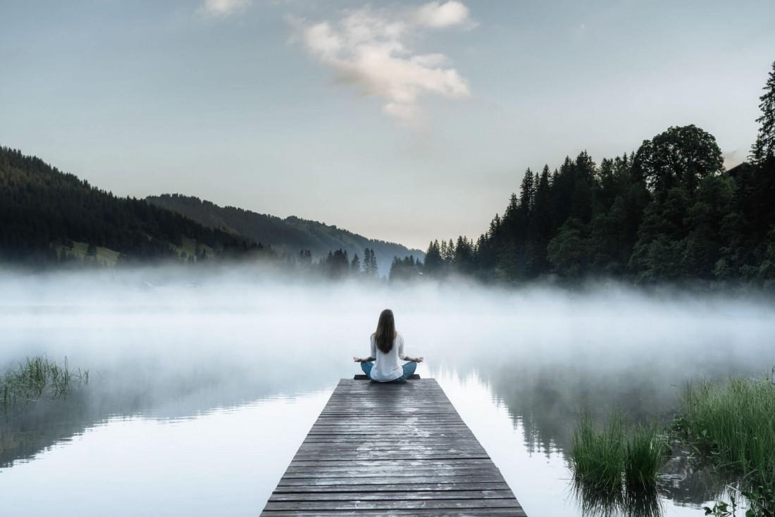 Méditation matinale face aux eaux calmes du lac de Lauenen © Destination Gstaad