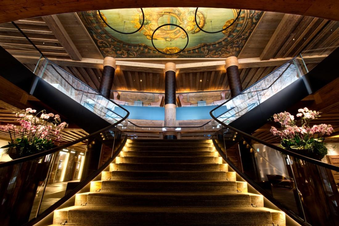 Un fastueux escalier à double révolution accueille les voyageurs arrivant à l'hôtel   © The Alpina Gstaad