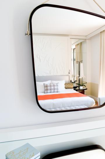 Ce grand miroir, évoquant un galet, est accroché au mur par des cordages et dissimule un écran de télévision © Royal Riviera