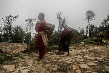 Deux femmes portent de lourds paniers chargés de vivres entre deux villages  | © Marion Brun
