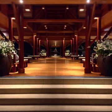 Bois, fleurs et éclairage tamisé dans le pavillon d'accueil de l'Amanpuri | © Yonder.fr
