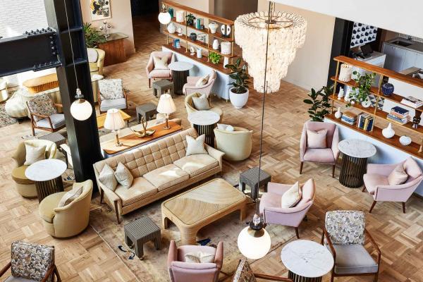Dans le lobby, de grandes poutres métalliques peintes en noir contrastent avec le parquet clair habillé de mobilier pastel.