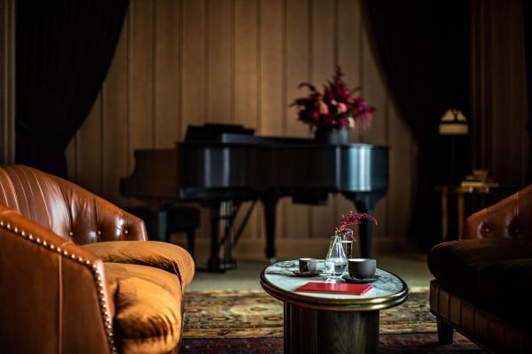 Un piano Steinway, fermé dans un coin, attend la soirée pour des performances intimistes.