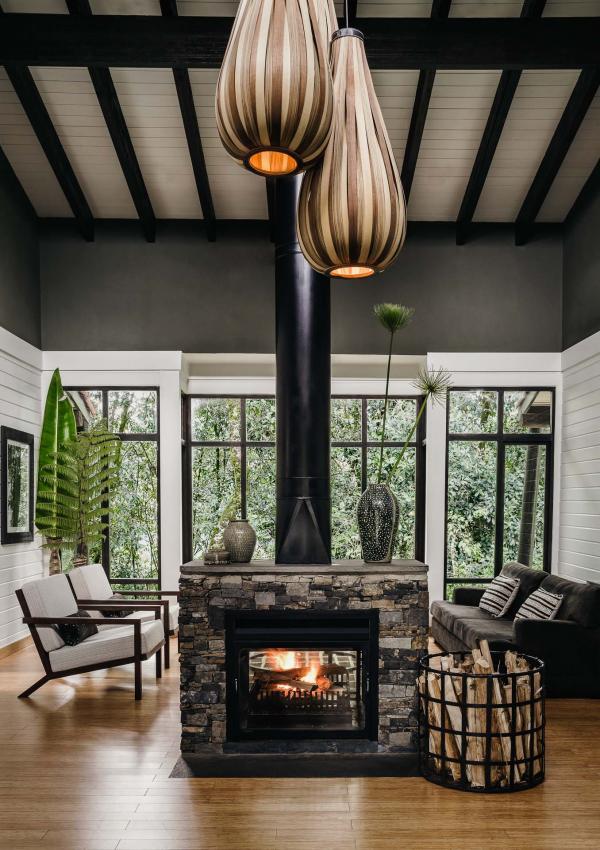 Le salon où brule un feu réconfortant et la terrasse privée en bois complète la chambre pour former un nid au milieu de la nature.