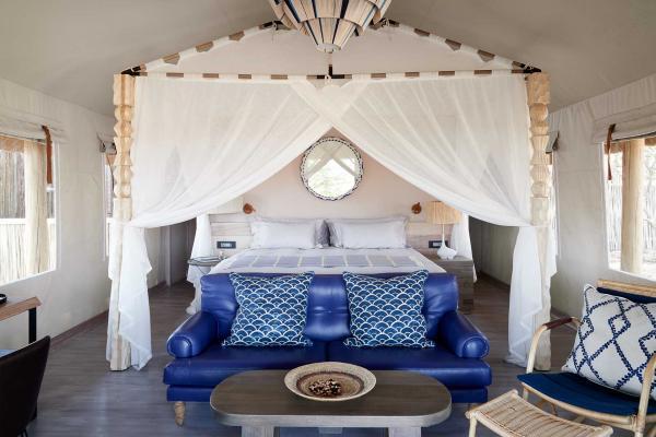Dotées d'un lit à baldaquin, d'un bureau et d'une élégante salle de bain, les chambres arborent d'éclatantes couleurs, contrastant avec la savane.