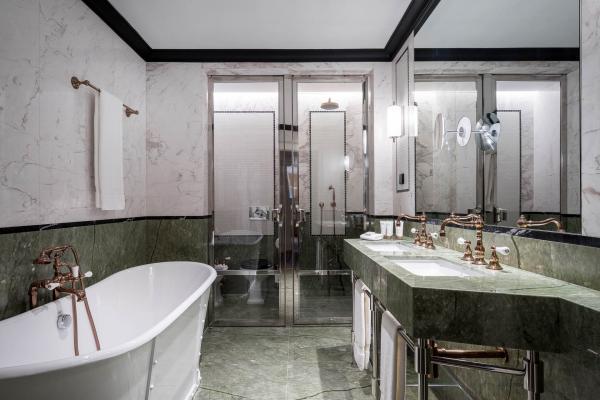 Dans les salles d'eau, les détails argent et or se marient avec le marbre blanc et vert.