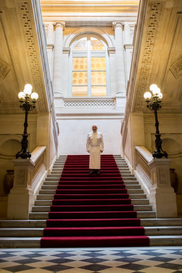 """Guy Savoy pose dans le grand escalier d'honneur de La Monnaie de Paris, son nouveau """"chez-lui"""" parisien © Laurence MOUTON"""