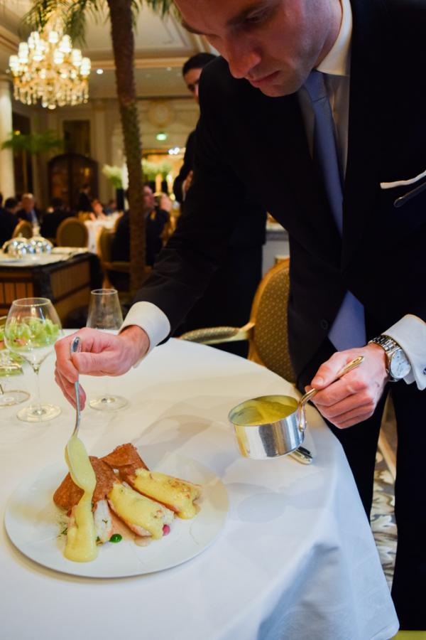 Le maître d'hôtel verse la mayonnaise tiède sur les langoustines © Yonder.fr