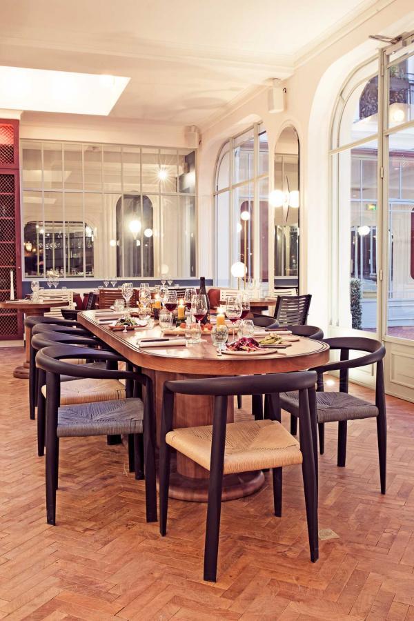 Une grande table d'hôtes, dans l'espace intérieur du restaurant © Karel Balas