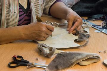 Une couturière découpe des morceaux de peau de phoque pour assembler un teddy bear.