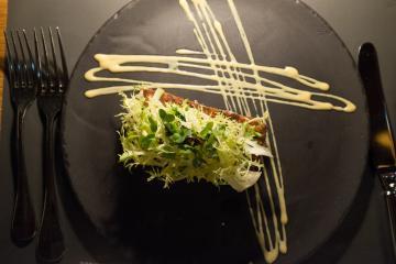 L'anguille tiède légèrement fumée se dissimule sous un fin croûton surmonté d'une rafraîchissante salade.