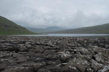 Les galets basaltiques à l'extrémité du lac de Leitisvtan, visible à l'arrière-plan.
