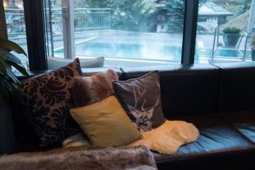 La banquette qui entoure la cheminée. Une bonne raison de la quitter ? Aller se tremper dans la piscine-jacuzzi de l'autre côté de la vitre ! © Yonder.fr