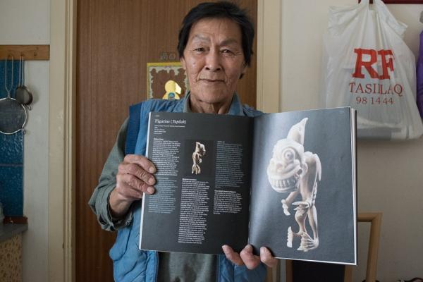 L'artiste Gideon Qeqe montrant le catalogue du Museum Volkenkunde de Leiden auquel figure un de ses tupilaks